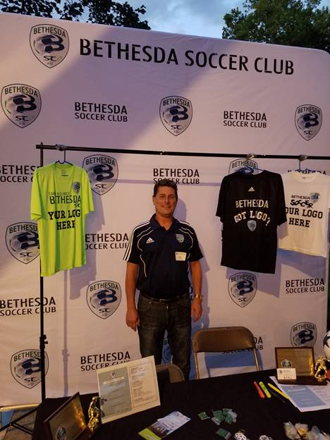 (l:r) Bethesda Soccer Club's Executive Director Brad Roos, displays his new backdrop at the Gaithersburg-Germantown Chamber non-profit showcase & membership picnic at Smokey Glen Farm. They are a select youth soccer club for ages 7-19. Learn more about them at www.bethesdasoccer.org.  (Photo credit –Laura Rowles, Director of Marketing, Gaithersburg-Germantown Chamber)